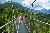 Woman walking on suspension bridge, Holzgau, Lechweg, valley of Lech, Tyrol, Austria