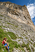 Woman having a break at fixed-rope route Pisciadu, fixed-rope route Pisciadu, Sella range, Dolomites, UNESCO World Heritage Site Dolomites, South Tyrol, Italy