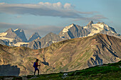 Woman hiking in front of glacier mountains of Ecrins, lake Lac du Serpent, Dauphine, Dauphiné, Hautes Alpes, France