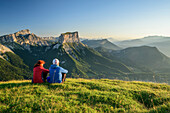 A man and a woman sitting on meadow and views of Grand Veymont and Mont Aiguille in the morning light, from the Tête Chevalier, Vercors, Dauphine, Dauphine, Isère, France