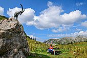 Woman while hiking sits on bank, Capricorn sculpture stands next to it, Lech source rocks, lechweg mountains, Vorarlberg, Austria