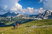 Two women while hiking, rising from the rötelstein Bischofsmütze and Gosaukamm Mountain in the background, rötelstein, Dachstein, Salzburg, Austria