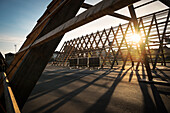 setting sun shines through wooden construction SALT (a nomadic art project) at dock of Langkaua close to Opera House, Oslo, Norway, Scandinavia, Europe