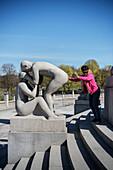 japanische Touristin in pinkem Oberteil dass an den Po einer Skulptur, der Vigeland Skulpturenpark des Bildhauers Gustav Vigeland, Frognerpark, Oslo, Norwegen, Skandinavien, Europa