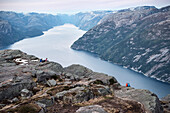 hikers sit on edge around Preikestolen and enjoy view at Lysefjord, Rogaland Province, Norway, Scandinavia, Europe