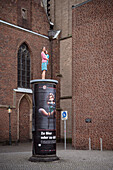 woman with child sculpture standing at advertising pillar in front of St. Lambertus church, historic town center, Duesseldorf, North Rhine-Westphalia, Germany