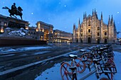 Bicycles parked in PIazza Duomo during snowfall at dusk. Milan, Lombardy, Northern Italy, Italy.