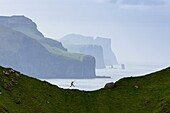 Man jumping on cliffs, Kalsoy island, Faroe Islands, Denmark.