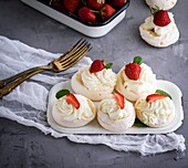 Baked meringue with cream and fresh strawberries, dessert pavlova.