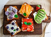 French toasts with soft cheese, strawberries, kiwi, walnuts, cherries and blueberries on a brown wooden board, breakfast.