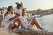 Family at beach, at sunset, one child. In holiday destination Chersonissos, Crete, Greece