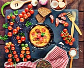 Black round frying pan with fried omelette, next to fresh ripe red cherry tomatoes, close up.
