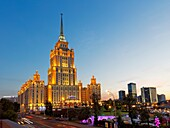 Radisson Royal Hotel Stalinist style high-rise building illuminated at dusk. Moscow, Russia.