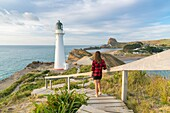 Woman descending the footpath towards Castlepoint lighthouse. Castlepoint, Wairarapa region, North Island, New Zealand.