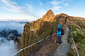 Woman admiring the view from PR1 trail. Pico do Arieiro, Funchal, Madeira region, Portugal.