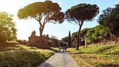 People running over the ruins of the ancient Via Appia (Appian Way) in Rome and man.
