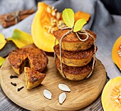 Stack of muffins with a pumpkin on a round wooden board and fresh pieces of pumpkin.