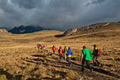 Visitors trek across the rolling hills in early morning sunlight, Torres del Paine National Park, Magallanes y de la Antartica Chilena, Patagonia, Chile, South America