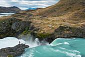 A visitor captures a photo at the Mirador Salto Grande waterfall, Torres del Paine National Park, Magallanes y de la Antartica Chilena, Patagonia, Chile, South America