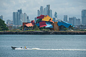 A power boat passes in front of the Panama City skyline featuring the colorful Biomuseo museum designed by Frank Gehry, Panama City, Panama, Central America