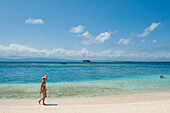 A woman in straw hat and bikini walks on the beach in front of a backdrop of turquoise water with a distant boat and islands, San Blas Islands, Panama, Caribbean