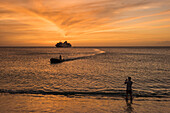Sunset scene of expedition cruise ship MS Hanseatic (Hapag-Lloyd Cruises) at anchor on the horizon, an approaching Zodiac and someone in the foreground taking a photograph, La Blanquilla Island, Venezuela, Caribbean