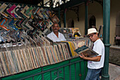 A salesman smiles into the camera while a customer searches for hidden treasures among the vinyl LP records, Belem, Para, Brazil, South America