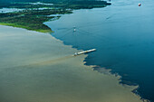 The Rio Negro (right) meets the Amazon River (also known as Rio Solimões), but the properties of the two water-bodies prevent swift mixing, creating a visual Meeting of Waters, Manaus, Amazonas, Brazil, South America