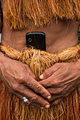 A member of the Witoto people (also Huitoto) carries a cell-phone tucked into the waist of his traditional apparel made of plant-fibers, Pebas (also Pevas), near Iquitos, Maynas, Peru, South America