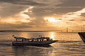 A small tour boat approaches the pier shortly before sunset, with the Ponte Rio Negro bridge visible in the background, Manaus, Amazonas, Brazil, South America