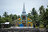 View of the brightly painted blue, white and yellow Catholic church surrounded by palm trees, Likiep Atoll, Ratak Chain, Marshall Islands, South Pacific