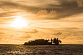 Late afternoon sun and wispy clouds paint the sky orange-yellow behind a small island covered with palms and other trees, Likiep Atoll, Ratak Chain, Marshall Islands, South Pacific