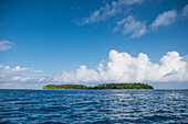 A long low-lying island lies in deep-blue seas under a sky dominated by large white clouds, Jabor Island, Jaluit Atoll, Ralik Chain, Marshall Islands, South Pacific