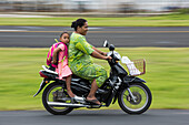 A woman in a green dress drives a motorscooter with a barefoot girl in a pink and white striped dress and a backpack sitting behind her, Fongafale Island, Funafuti Atoll, Tuvalu, South Pacific