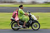 Eine Frau in einem grünen Kleid fährt einen Motorroller mit einem barfüßigen Mädchen in einem rosa-weiß gestreiften Kleid samt Rucksack, Fongafale Island, Funafuti Atoll, Tuvalu, Südpazifik