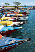 Numerous small, colorful, mostly wooden boats lie closely packed alongside a causeway, Lautoka, Viti Levu, Fiji, South Pacific