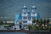 The blue, white and black Immaculate Conception Cathedral (also called Cathedral of Apia or Mulivai Cathedral), built on the site of the original mid-19th-Century church and opened in 2014, rises above nearby palm trees close to the shore, Apia, Upolu, Sa