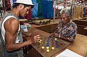 Market workers bide their time with a game of checkers using blue and yellow bottle caps, Apia, Upolu, Samoa, South Pacific
