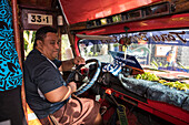 A bus driver wearing the traditional ie lavalava, a skirt-like piece of clothing worn by men and women, prepares to drive a group of expedition ship passengers on an excursion, Fagamalo, Savai'i, Samoa, South Pacific