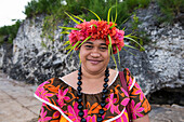 A local woman wearing a brightly colored flower-print dress, a necklace made of large seeds, and a headdress of flowers and leaves smiles into the camera, Atiu, Cook Islands, South Pacific