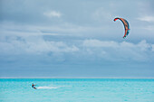 A kite-boarder cuts through turquoise waters on a blue-clouded day, Bora Bora, Society Islands, French Polynesia, South Pacific