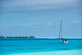 A small anchored sailboat sits in turquoise water in the foreground, while in the background a line of thatch-roofed overwater bungalows on stilts from a luxury resort is visible, Bora Bora, Society Islands, French Polynesia, South Pacific