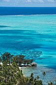 A bungalow stands on a small land-spit, surrounded on three sides by shallow turquoise water, Bora Bora, Society Islands, French Polynesia, South Pacific