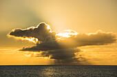 The late afternoon sun breaks through thunderheads, creating a warm, orange-yellow light, Bora Bora, Society Islands, French Polynesia, South Pacific