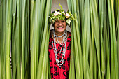 A local woman wearing a red flower pattern dress, a seed necklace, and a headdress of flowers and ferns, smiles from among a curtain of green leaves, Rimatara, Austral Islands, French Polynesia, South Pacific