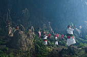 Locals, some in traditional costume, greet visiting tourists in the mouth of a huge cave, Rurutu, Austral Islands, French Polynesia, South Pacific