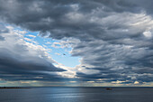 A ship makes way under a sky filled with oddly formed coulds, while a lone bird flies in front of an opening in the cloud-cover, Punta Arenas, Magallanes y de la Antartica Chilena, Patagonia, Chile, South America
