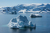 Icebergs drift in the bay in front of a snow-covered mountain range, Wilhelmina Bay, Antarctic Peninsula, Antarctica