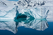 A rare, windstill moment creates a mirror-image of an ice formation featuring a low arch, Wilhelmina Bay, Antarctic Peninsula, Antarctica