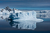In a rare, virtually wind-still moment, a mirror-image is created from a large iceberg, occupied by a single Chinstrap penguin (Pygoscelis antarcticus), and surrounding mountains, Wilhelmina Bay, Antarctic Peninsula, Antarctica